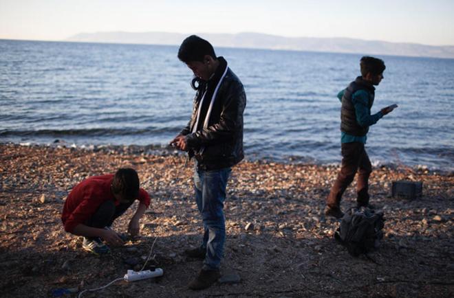 Người tị nạn sạc điện thoại tại Lesbos. Ảnh: Cnet.