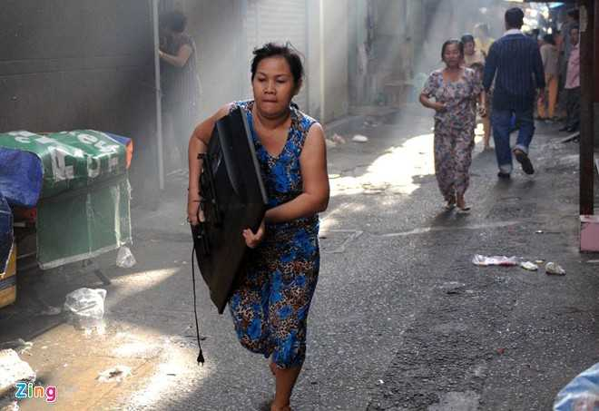 Một phụ nữ ôm tivi chạy khỏi đám cháy
