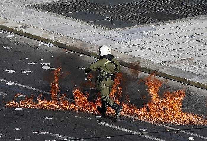 Một cảnh sát chống bạo động chạy qua ngọn lửa gây ra lúc đụng độ giữa cảnh sát và người biểu tình ở Athens, Hy Lạp ngày 12/11