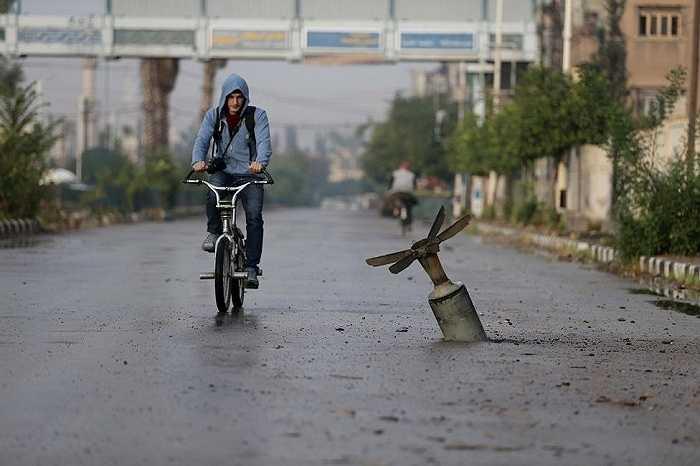 Một thanh niên đi qua khu vực quả bom phát nổ tại thị trấn Douma, Đông Ghouta ở Damascus, Syria ngày 5/11