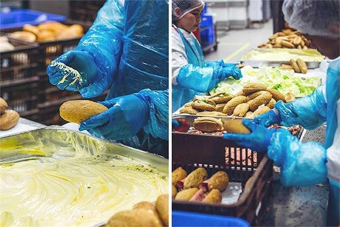 Đội ngũ làm bánh làm việc rất nhanh chóng và hiệu quả. Không cần dùng đến dao, họ sử dụng găng tay rồi phết đều bơ lên các miếng bánh mỳ trước khi kẹp chúng với rau diếp và những lát thịt nguội.