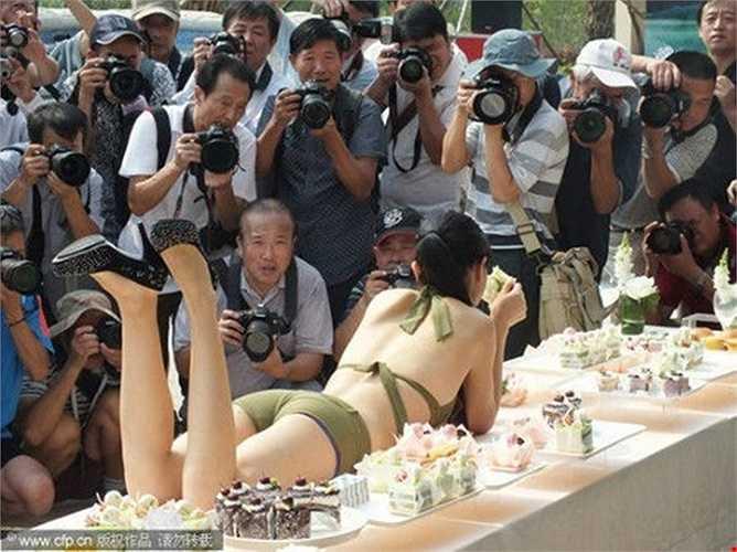 Chiêu dùng gái đẹp để câu khách mua nhà: Các nhà kinh doanh bất động sản tại Trung Quốc đã tìm đủ mọi cách để thu hút khách hàng từ việc thuê người đẹp trình diễn tới việc vẽ lên người họ. Ảnh: Người mẫu nằm trên bàn tiệc tại hội chợ nhà đất ở Yichang, tỉnh Hồ Bắc, Trung Quốc.