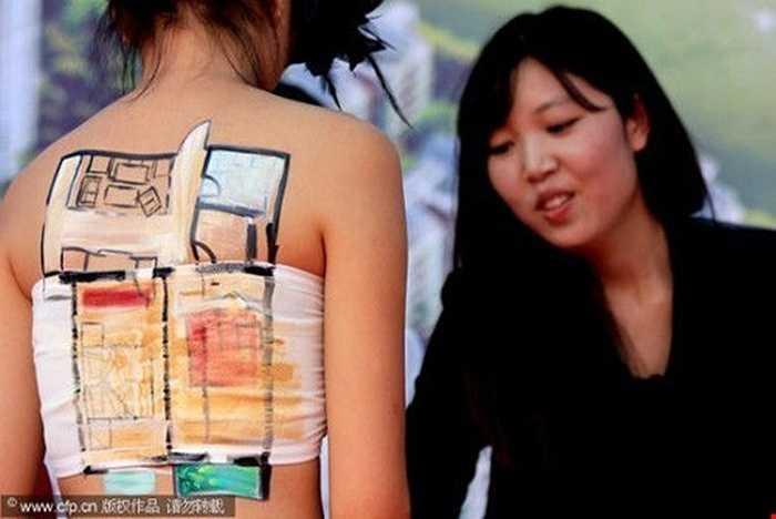 Vẽ mẫu căn hộ lên cơ thể người mẫu để thu hút khách mua nhà ở thành phố Zhoukou, tỉnh Hà Nam.