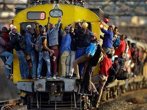 Những người dân may mắn chức mừng bản thân với việc có thể lên một chuyến tàu ở Soweto, Nam Phi mặc dù phải bám vịn leo trèo