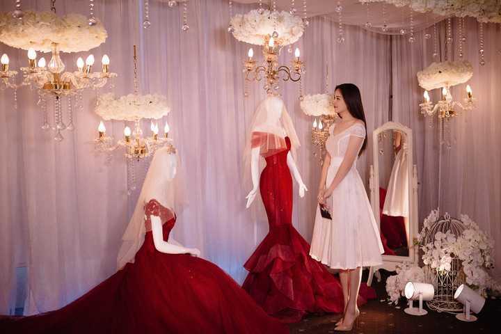"""Không chỉ thăm quan, người đẹp cũng tinh nghịch đội thử một chiếc vương miện được trưng bày tại đây. Hoa hậu Việt Nam bày tỏ: """"Những chiếc váy cưới ở đây khiến tôi phải xuýt xoa bởi sự phối hợp tinh xảo, đầy ngẫu hứng giữa ren hoa lãng mạn và pha lê lấp lánh""""."""