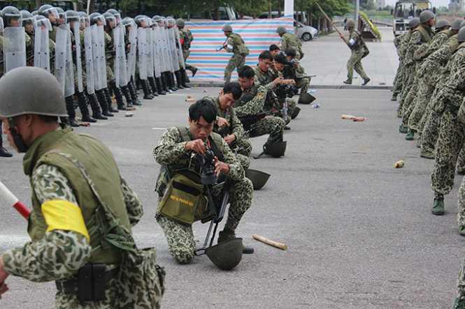 Lực lượng bộ đội hóa học khẩn trương đeo các thiết bị hỗ trợ phòng độc để làm nhiệm vụ khi đám đông biểu tình sử dụng bom khói tấn công