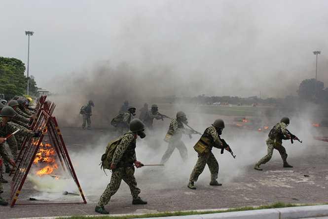 Các chiến sĩ bộ đội hóa học tiến về phía trước trong làn khói độc làm nhiệm vụ