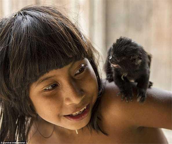 Một em bé chơi đùa với một loài động vật hoang dã mà người dân nơi đây coi chúng như những vật nuôi trong gia đình