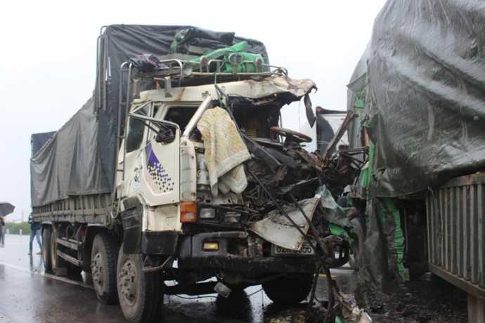 Sau cú đâm, đầu xe tải nát bét, tài xế xe tải trọng thương.