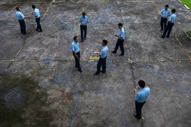 Các phi công trẻ chăm chú theo dõi bài giảng của thầy, đàn anh và đồng đội khác tại sân tập bay mô hình Su30mk2 - Ảnh: Thuận Thắng