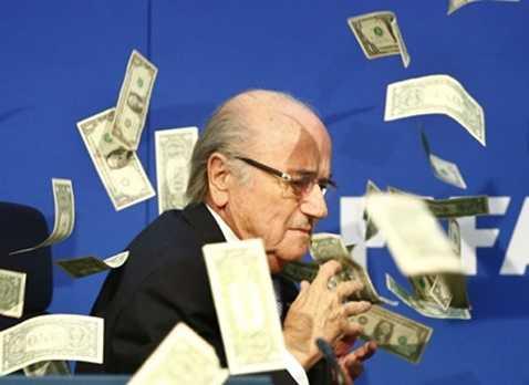 Sepp Blatter bị danh hài người Anh Simon Brodkin ném một xấp tiền vào mặt