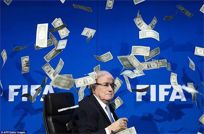 Chủ tịch FIFA Sepp Blatter ngồi giữa đống USD đang rơi xuống do danh hài người Anh ném vào ở Zurich hồi tháng 7
