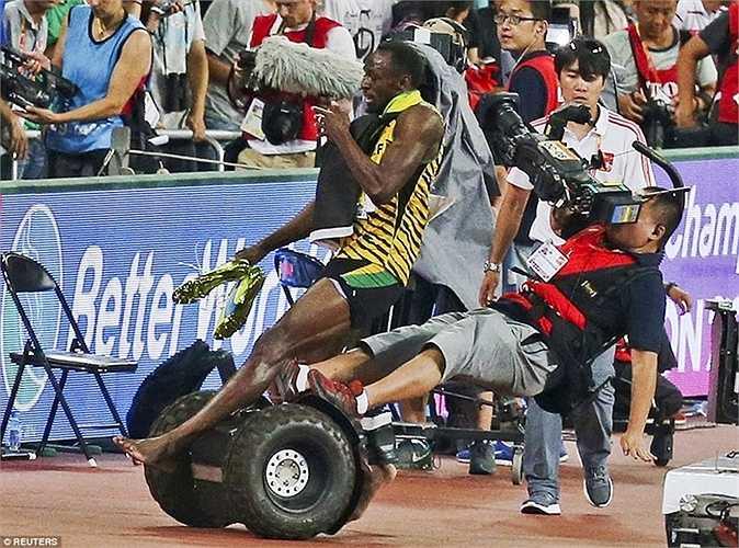 'Tia chớp' Usain Bolt bị một người quay phim đốn ngã khi đang ăn mừng chiếc HCV ở đường chạy 200m tại giải VĐTG