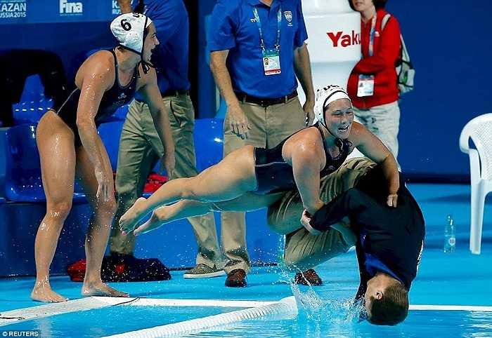 Các nữ VĐV bóng nước của ĐT Mỹ cố gắng ngăn HLV Adam Krikorian ăn mừng chiếc HCV giành được ở giải VĐTG bơi lội tổ chức tại Kazan trong tháng 8