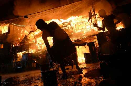 Người dân địa phương cố gắng chữa cháy tại một khu ổ chuột ở Manila. Ảnh: AFP
