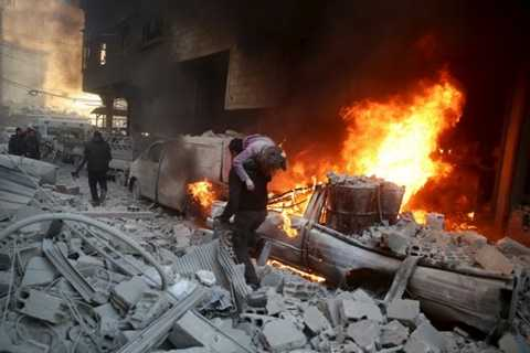 Người cha vác đứa con bị thương đưa đi cứu nạn tại thị trấn Douma sau khi bị trúng bom đạn của lực lượng thân chính phủ al-Assad ngày 30/12 - Ảnh: Reuters