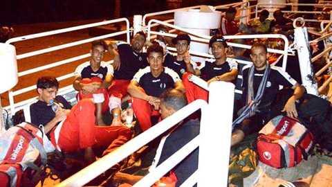 Các cầu thủ ĐT Yemen lên thuyền di chuyển tới châu Phi, phía sau họ là những người di cư