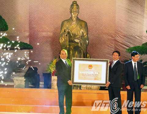 Phó Thủ tướng Chính phủ Nguyễn Xuân Phúc trang Bằng xếp hạng di tích Quốc gia đặc biệt cho Đền thờ Trạng trình Nguyễn Bỉnh Khiêm - Ảnh MK