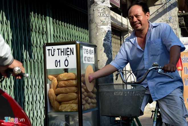 Ông Tư, một lao động tại khu phố ghé tủ, phấn khởi lấy 2 chiếc. Ngoài ra còn có một số người dân sống xung quanh cũng đến lấy bánh về.