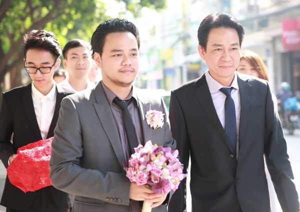 Đạo diễn Hoàng Duy mặc vest xám, cầm hoa cưới cùng người thân và đoàn bưng tráp quả nhà trai vào làm lễ xin dâu.