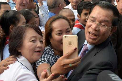 Thủ tướng Hun Sen thể hiện hình ảnh trẻ trung khi chụp selfie với dân chúng - Ảnh: AFP