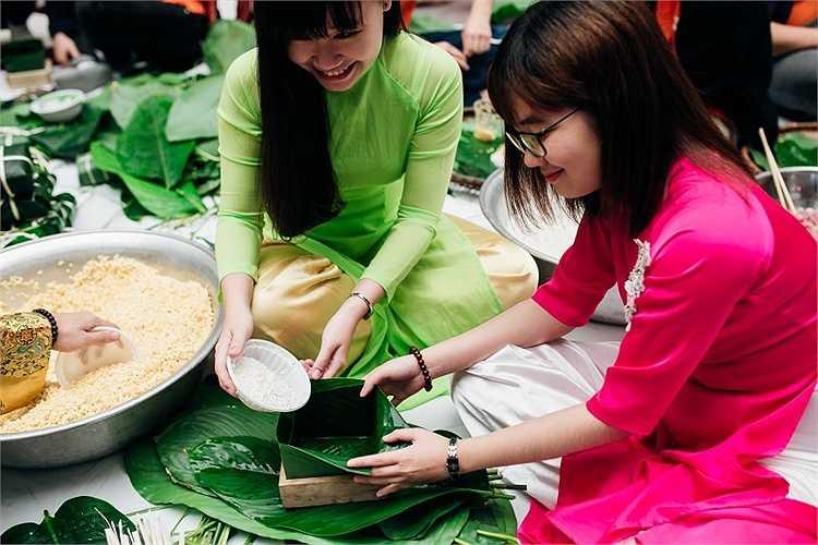 Nữ sinh ĐH FPT cũng thích thú khi được tự tay trải nghiệm việc gói bánh chưng