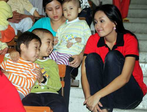 Khoảnh khắc Hoa hậu Việt Nam 2006 Mai Phương Thúy giản dị, thân mật ngồi bệt xuống bậc thang khán đài chuyện trò cùng các em nhỏ trong một chuyến đi từ thiện