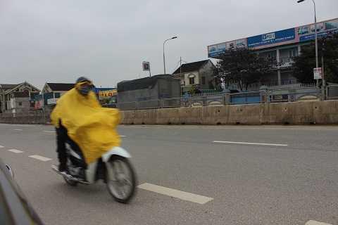 Người dân tham gia giao thông mặc áo mưa để để hạn chế cái rét