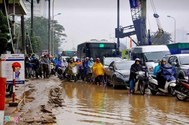 Nước ứ đọng chiếm phần lớn lòng đường vốn đã nhỏ hẹp vì công trường khiến xe cộ gần như không thể lưu thông.
