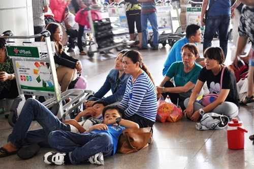 Nhiều gia đình mỏi mòn ngồi bệt dưới sàn gạch. Ảnh Việt Văn