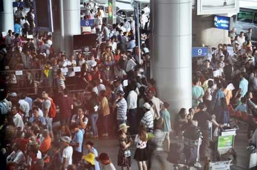 """Trái ngược với không khí khá thông thoáng ở các nhà ga, bến xe thì tại sân bay Tân Sơn Nhất lại """"nóng"""" lên khi có hàng nghìn người dân đổ về đây đón Việt kiều. Ảnh Việt Văn"""