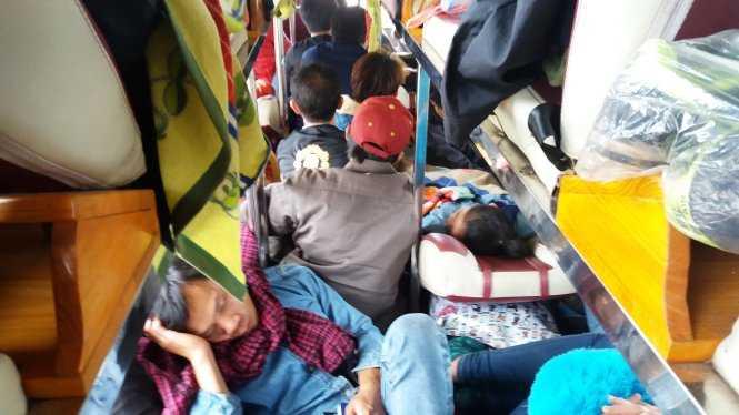 Hành khách nằm ngồi chen chúc trên chuyến xe từ Lào về quê - Ảnh: Doãn Hòa