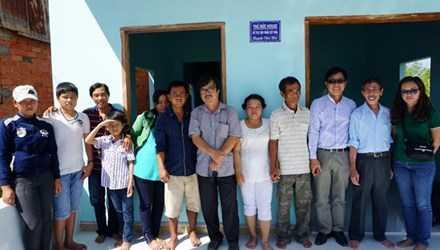Gia đình ông Huỳnh Văn Nén, các phóng viên báo Tiền Phong cùng đồng nghiệp trước cửa căn nhà đang được hoàn thiện.