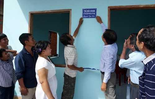 Mọi người cùng vui khi tấm biển nhà mới được ông Nén và nhà báo Nguyễn Đại Dương, Phó trưởng Ban Hợp tác truyền thông, báo Tiền Phong gắn lên tường trước nhà.
