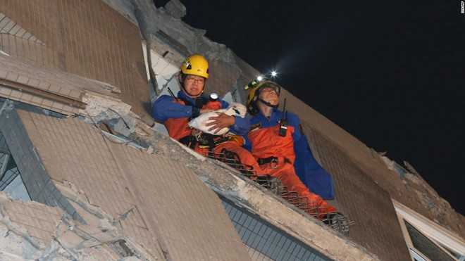 Đội cứu hộ bế một em bé ra khỏi hiện trường vụ sập chung cư do động đất. Đến 8h30 (giờ Hà Nội), một lính cứu hỏa cho biết anh và các đồng nghiệp đã giúp đưa hơn 100 người ra ngoài an toàn. Sở Cứu hỏa Đài Nam cho biết những người này đã được đưa đến các bệnh viện để điều trị vết thương. Ảnh: Reuters