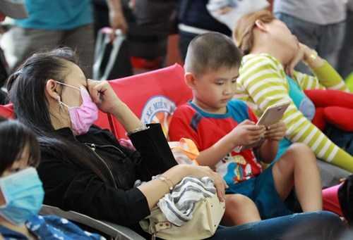 Để tranh kẹt xe, nhiều người tranh thủ ra sớm phải ngồi vật vạ trên ghế chờ Bến xe miền Đông. Trong ảnh, người mẹ và người dì ngủ gục bên đống valy mặc con chơi điện thoại.