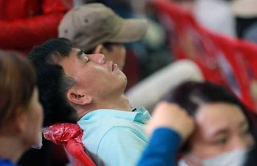 Người đàn ông sau khi giao đống đồ cho vợ coi cũng tranh thủ ngả đầu ra ghế ngủ tạm trong lúc chờ xe.