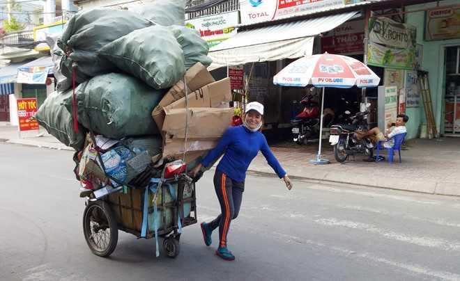 Chị Hồng rạng rỡ bên chuyến xe chở đầy ve chai mua được những ngày cuối năm. Ảnh: Trường Nguyên.