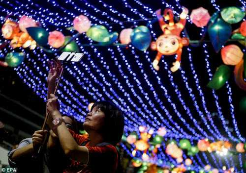 Mọi người chụp ảnh dưới ánh đèn trang trí ở Hong Kong.