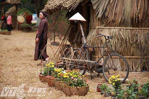 Đình ảnh cổng làng, ụ rơm, xe kéo… quen thuộc được sắp đặt khéo léo giữa muôn vàn sắc hoa.