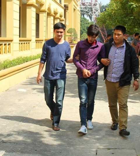 Phạm Minh Vương (giữa) dẫn giải về trụ sở công an