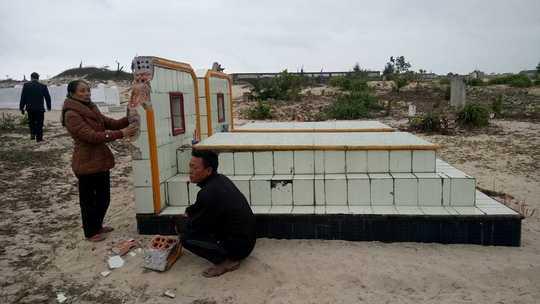 Vợ chồng bà Nguyễn Thị Xinh bên bên mộ phần dòng họ bị đập phá.