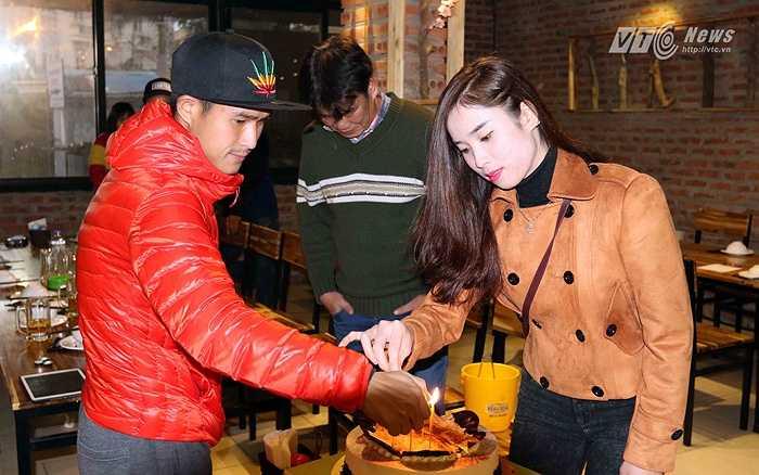 Quốc Long cùng một fan nữ của Hà Nội T&T thắp nến lên bánh tiệc cảm ơn những đóng góp của HLV Phan Thanh Hùng. (Ảnh: Quang Minh)