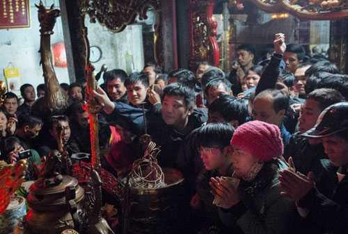 Người dân chen nhau, cố với tay thật xa để quẹt tiền hoặc chạm được thanh kiếm linh thiêng ở trong hậu cung trong lễ khai ấn năm 2015.