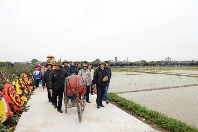 Đoàn người đưa tiễn kéo dài  hơn 1 cây số dọc đường làng ra nghĩa trang, đi giữa hai hàng đào phai đang nở hoa giữa giá rét.