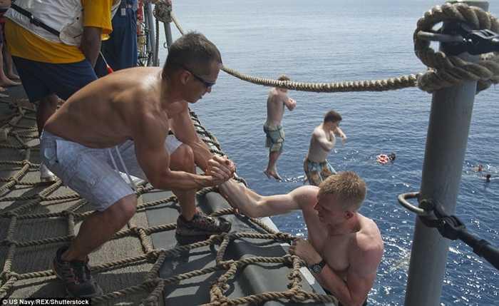 Các thủy thủ kéo nhau lên tàu sau khi bơi lội thỏa thích