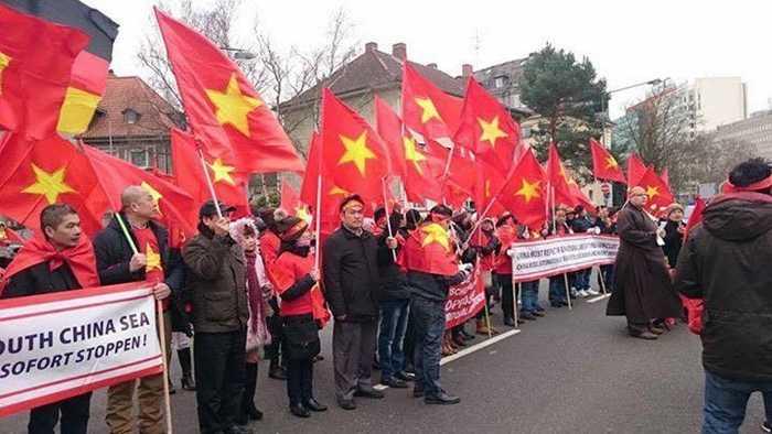 Những người biểu tình mang theo băng rôn và quốc kỳ Việt Nam