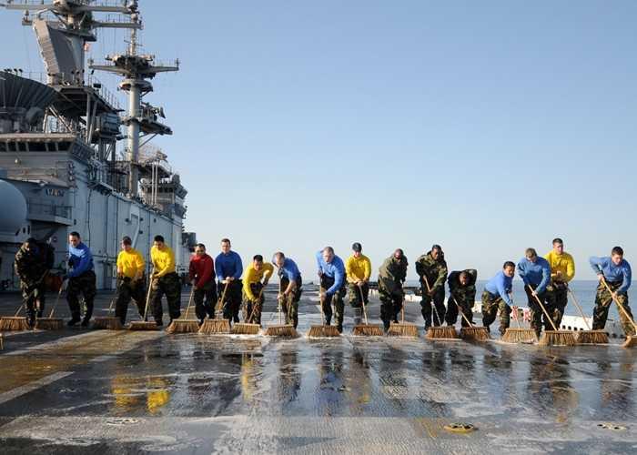 Các thủy thủ dọn dẹp sàn bay sau khi kết thúc nhiệm vụ