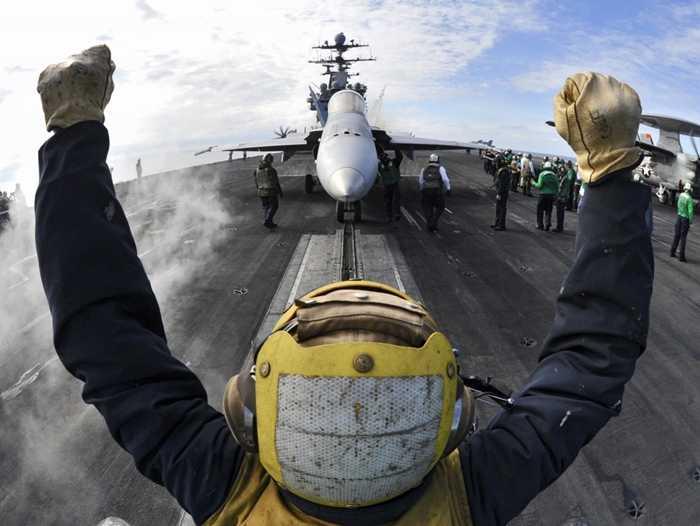 Hoa tiêu chỉ dẫn cho F/A-18C Hornet di chuyển trên sàn của tàu sân bay  USS Harry S. Truman