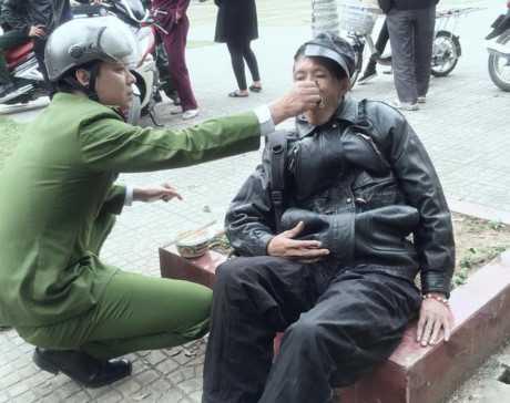 Chiến sĩ công an đút đồ ăn cho người đàn ông ngất xỉu bên đường. Ảnh: Phạm Lệ Thủy.
